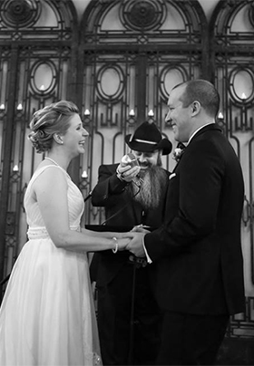 A black and white photo of Jon performing a wedding, with a smiling bride and groom.