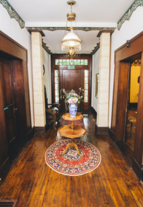 The front hallway of the Old Caledonian, with wooden floors and staircase, is pictured.
