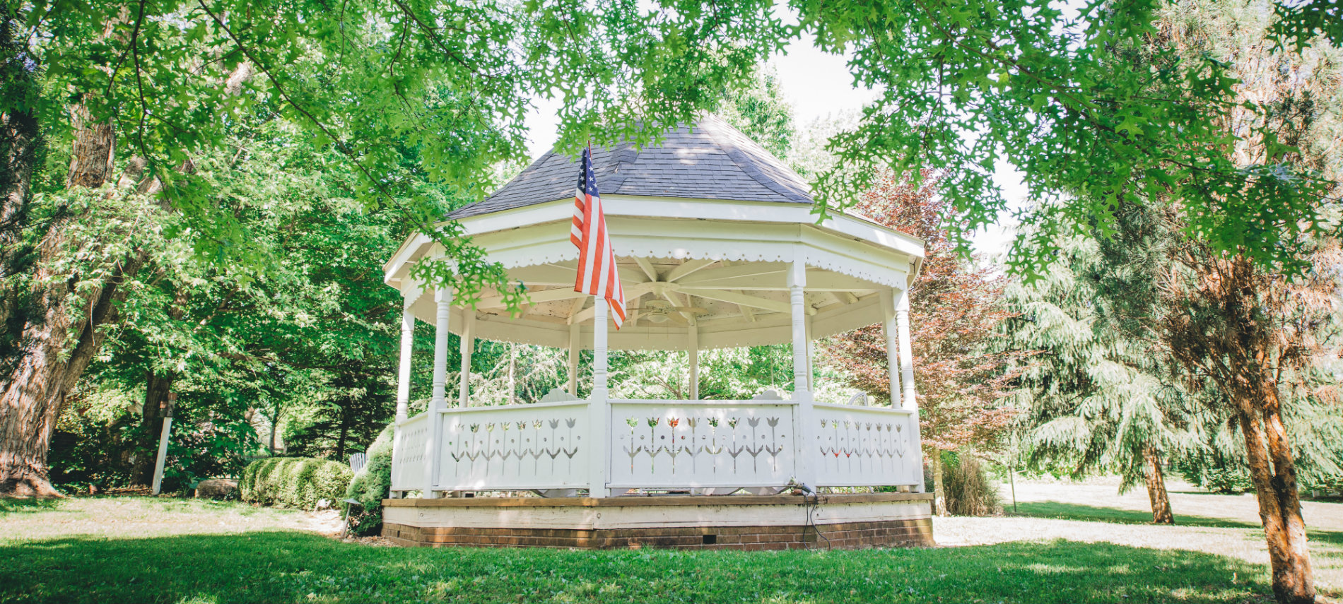 The Old Caledonian's stately gazebo, with green grass and tree boughs, is pictured.