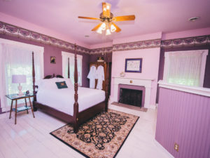 The Heather Room, with a purple color scheme and four post bed, is pictured.