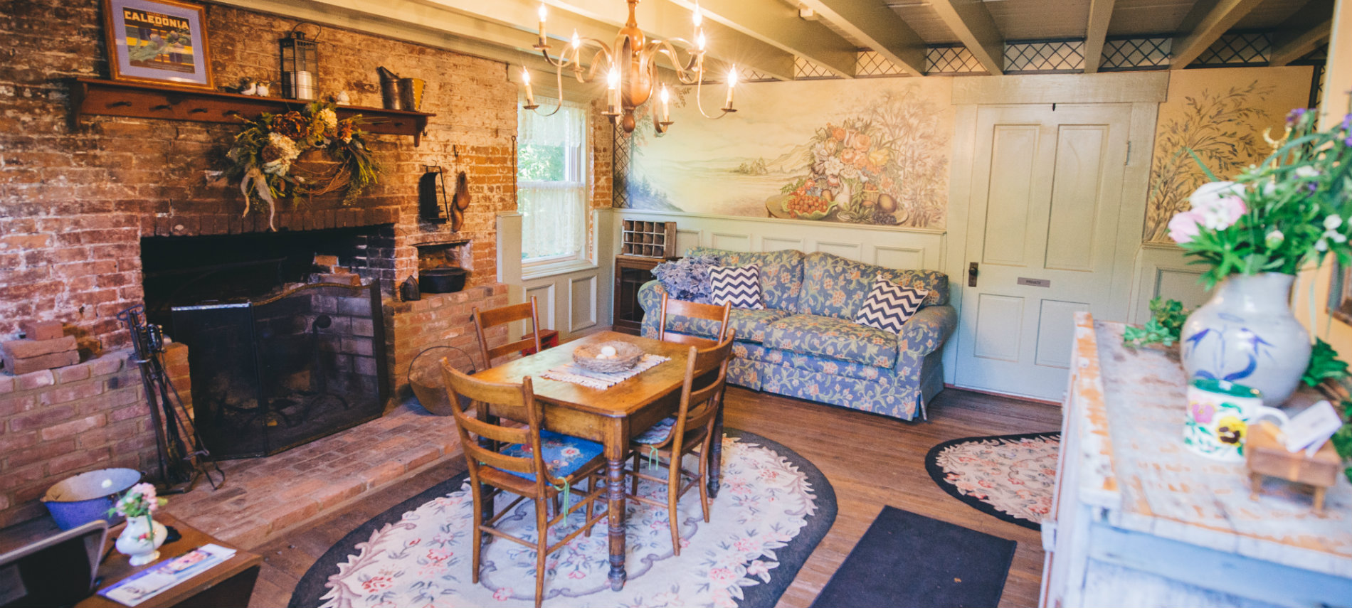 The beautiful Keeping Room at the Old Caledonian B&B, with a colorful mural and period furnishings, is pictured.