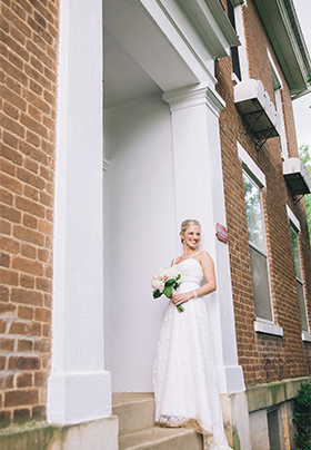 A beautiful bride, bouquet in hand, stands at the portico of the Old Caledonian B&B.