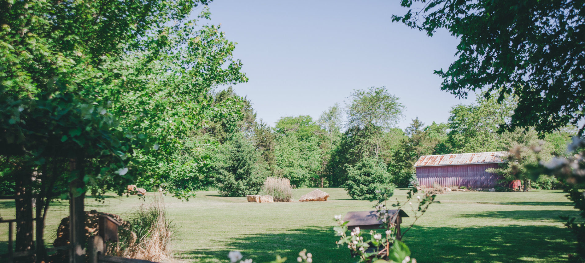 The large backyard of the OCBB with trees and red barn